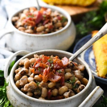 Two bowls of Southern black eyed peas recipe topped with bacon