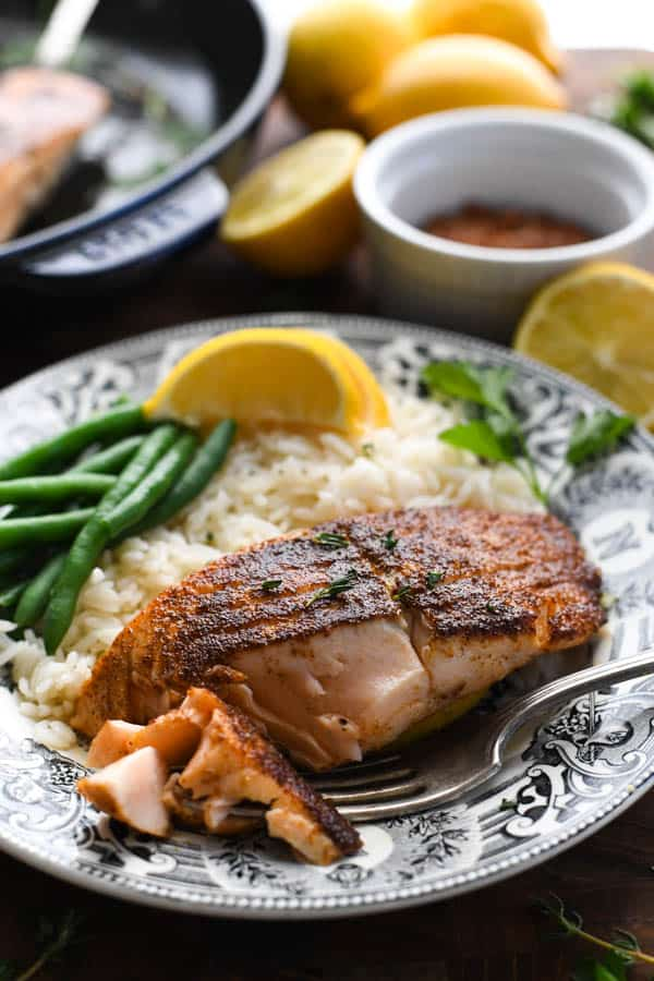 Front shot of a piece of blackened salmon on a plate with green beans and rice