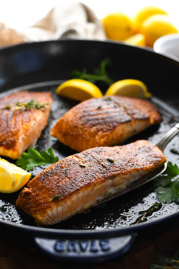 Cast iron salmon recipe with lemon wedges and fresh herbs