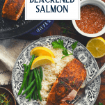 Overhead shot of a piece of blackened salmon on a plate with sides and text title overlay