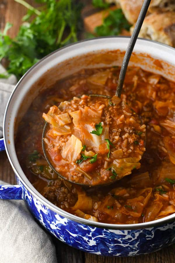Close up shot of a ladle in a pot of stuffed cabbage roll soup