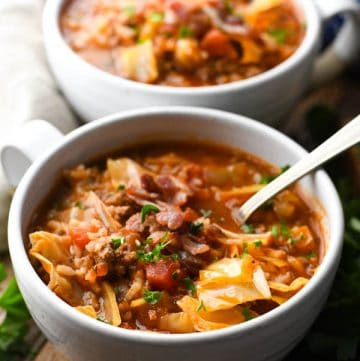 Close up shot of stuffed cabbage roll soup recipe served in two white ceramic bowls