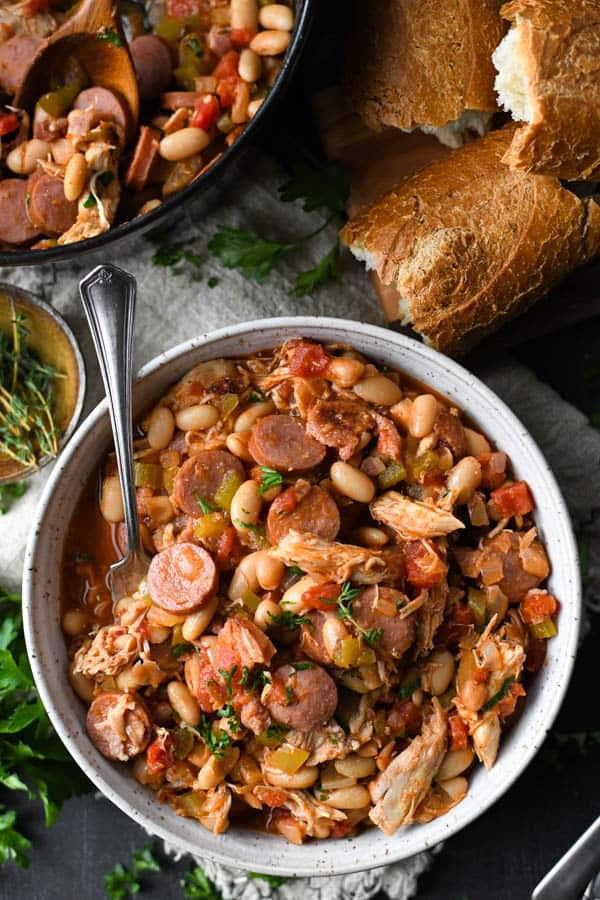 Overhead shot of a bowl of white bean chicken cassoulet with french bread