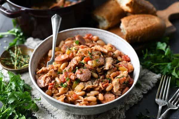 Horizontal shot of a bowl of chicken cassoulet on a table with bread