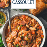 Overhead shot of a bowl of chicken and sausage cassoulet with text title overlay