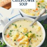 Cream of cauliflower soup recipe served in two white bowls with text title overlay