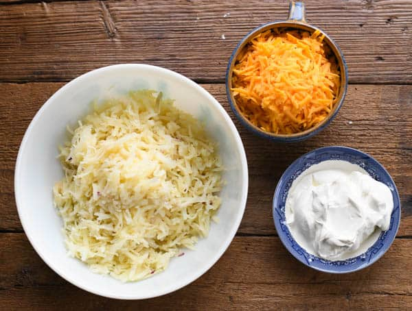 Ingredients for potato casserole with shredded potatoes cheese and sour cream