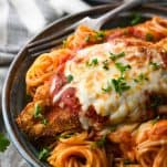 The best chicken parmesan recipe garnished with fresh parsley and served over spaghetti