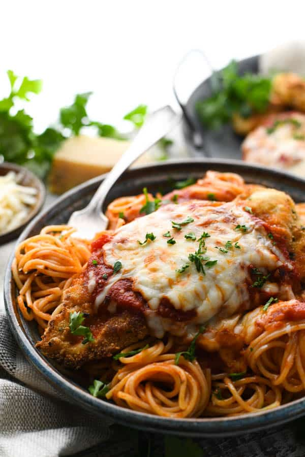 Plate of homemade chicken parmesan served with spaghetti