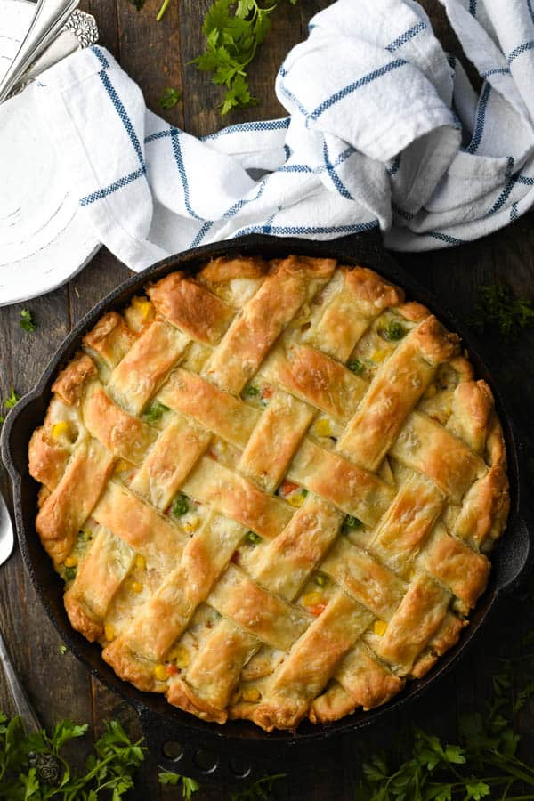 Overhead image of a made from scratch chicken pot pie with a lattice top crust in a cast iron skillet