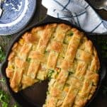 Overhead image of a homemade chicken pot pie on a wooden table with fresh parsley garnish