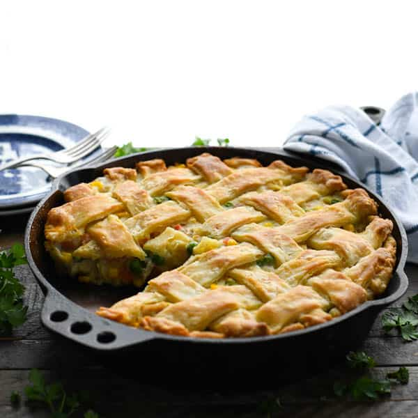 Square image of a chicken pot pie in a cast iron skillet on a wooden table