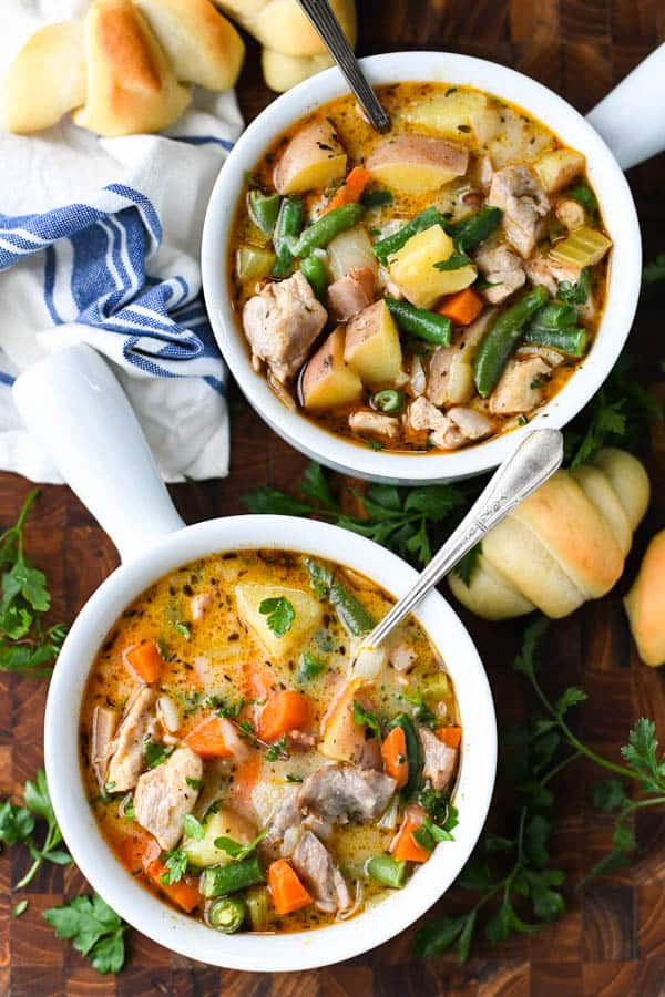 The best chicken stew recipe served in two white bowls with crescent rolls on the side