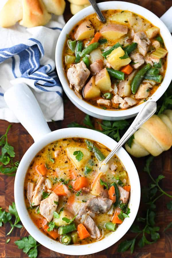 Close overhead image of chicken potato stew served in two white bowls