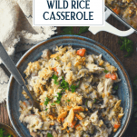 Overhead shot of a bowl of baked chicken and wild rice casserole with text title overlay