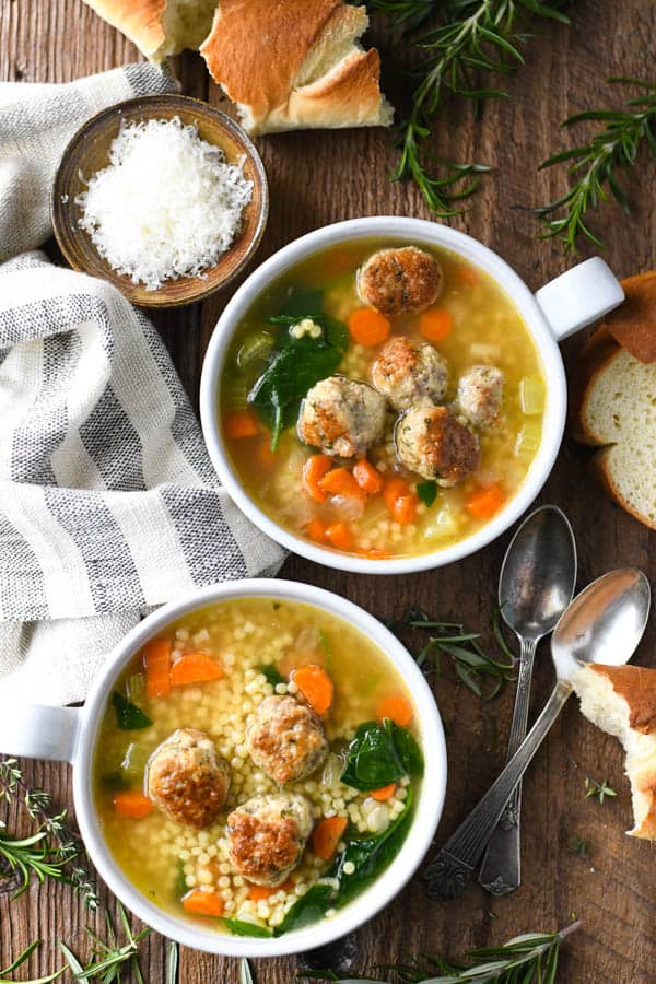 Overhead image of two bowls of grandma's Italian Wedding Soup on a wooden table