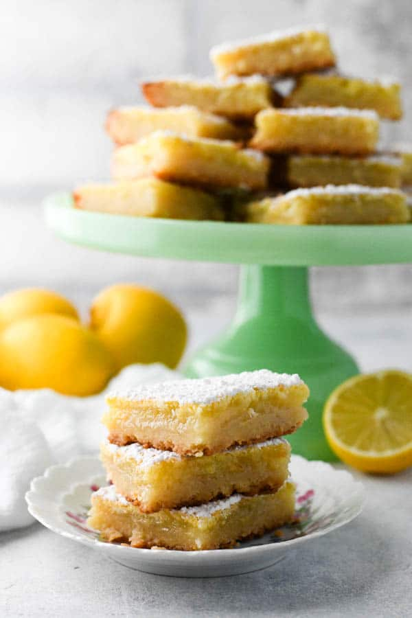 Side shot of a small plate full of the best lemon squares stacked