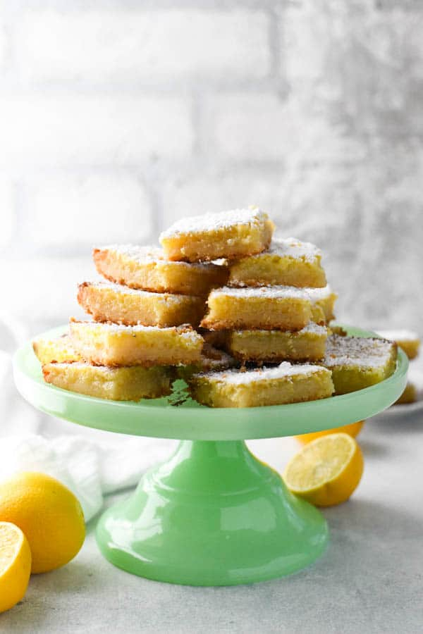 Front shot of easy lemon squares served on a green cake stand