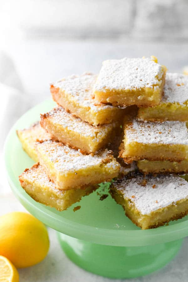 A green tray of classic lemon bars dusted with powdered sugar.