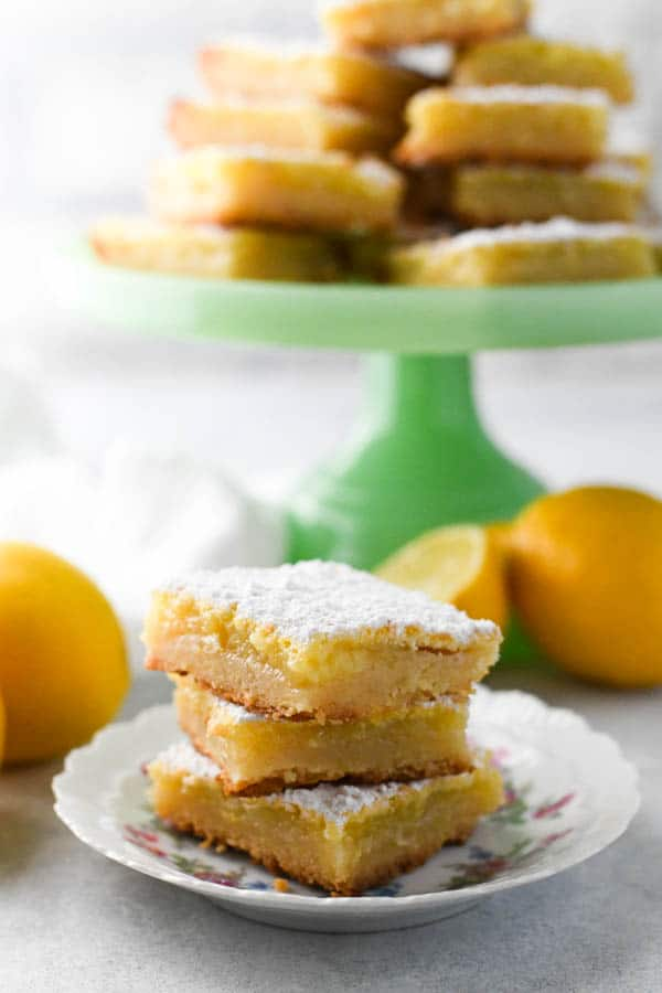Three creamy lemon squares with shortbread crust on a small white plate