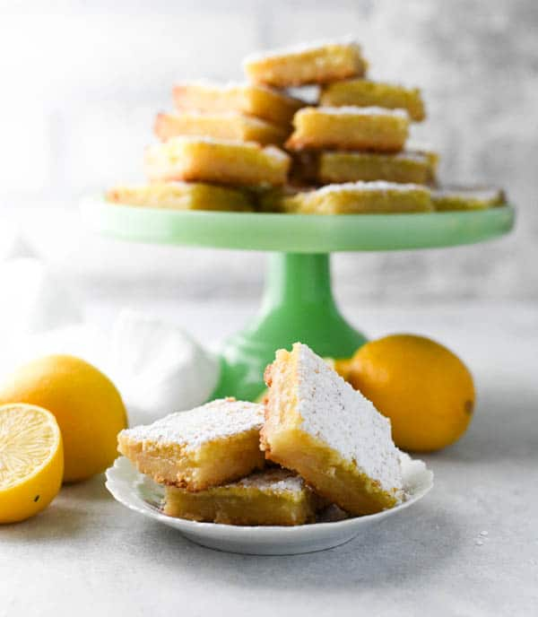 Front shot of old fashioned lemon squares recipe served on a white table among fresh lemons