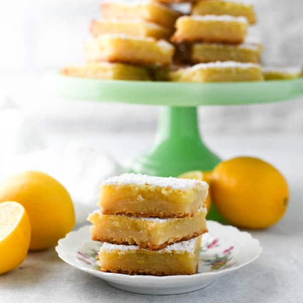 Square shot of lemon bars with shortbread crust on a small white plate