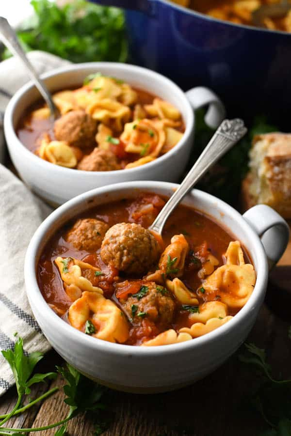 Side shot of two bowls of tortellini and meatball soup on a table