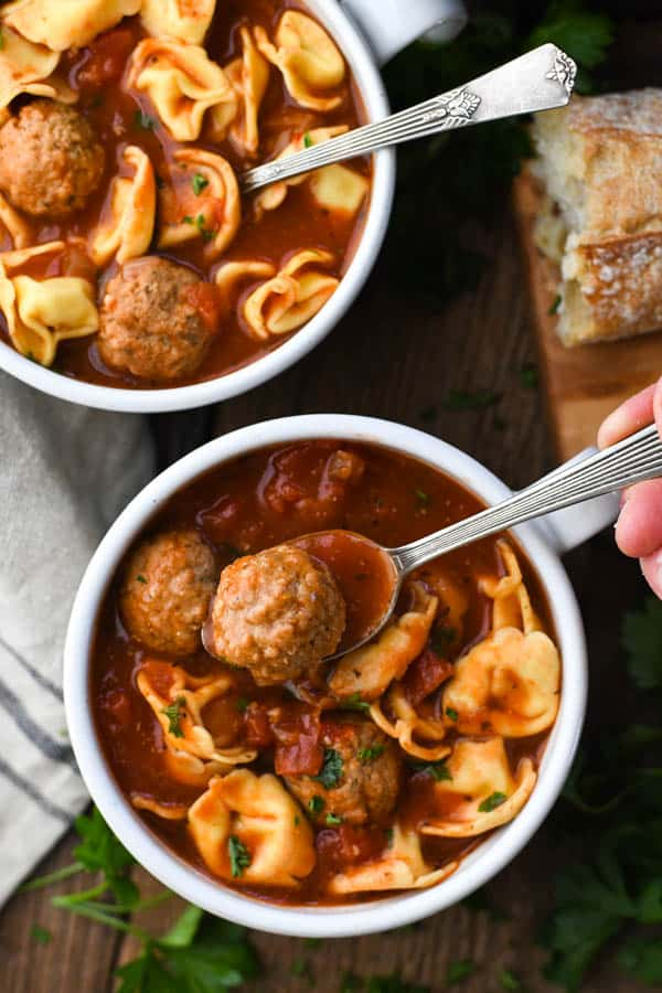 Overhead shot of a spoon in a bowl of meatball soup with cheese tortellini