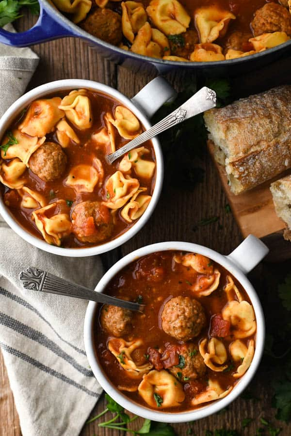 Overhead shot of two bowls of tortellini and meatball soup with a side of bread