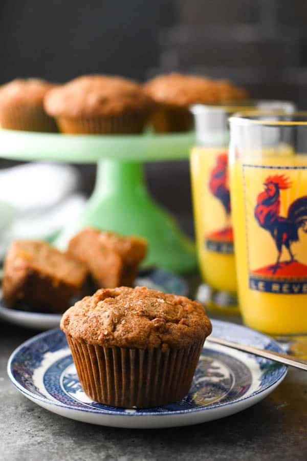 Side shot of healthy morning glory muffins on a breakfast table with orange juice