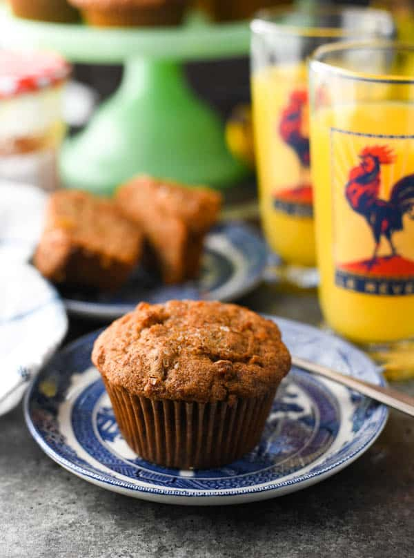 Front shot of the best morning glory muffins on a plate with orange juice in the background