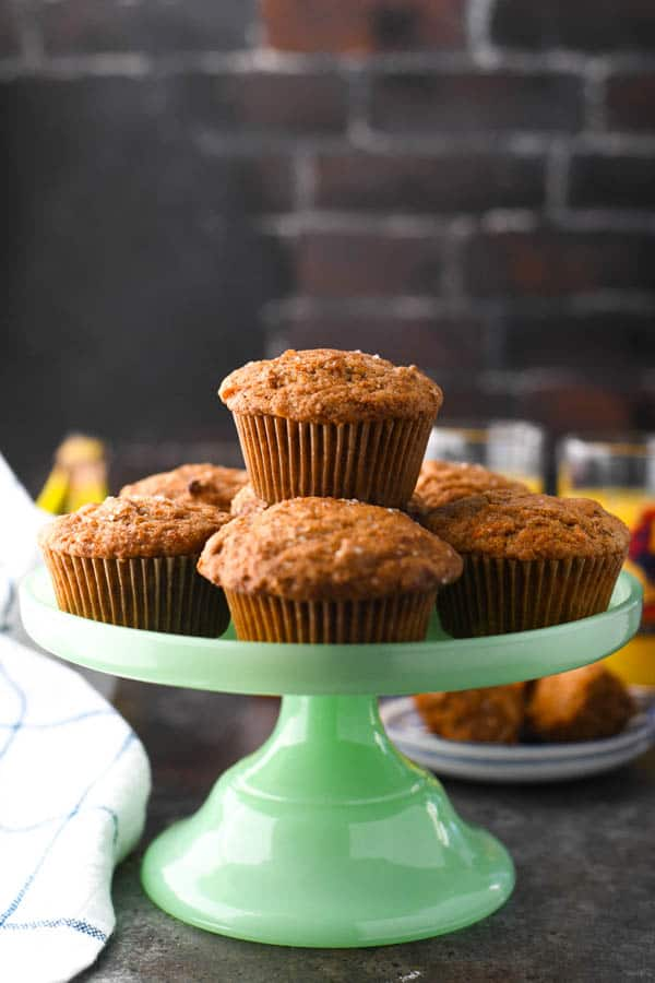Front shot of homemade morning glory muffins on a green cake stand.