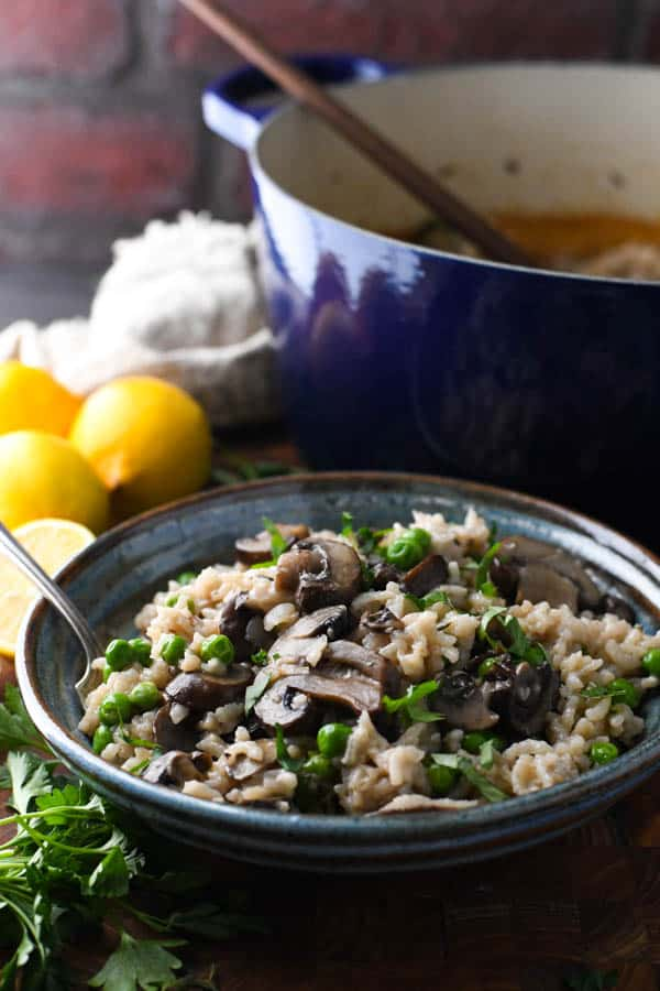 Side shot of a bowl of easy mushroom risotto in front of a Dutch oven with a brick wall