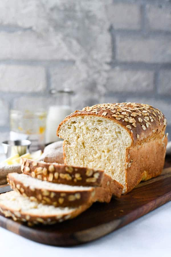 Front shot of farmhouse oatmeal bread on a wooden board in front of a white backdrop