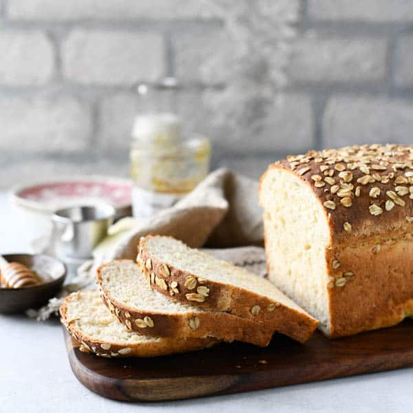 Square shot of a sliced loaf of easy oatmeal bread in front of a white brick wall