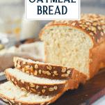 Front shot of a sliced loaf of classic homemade oatmeal bread with text title overlay