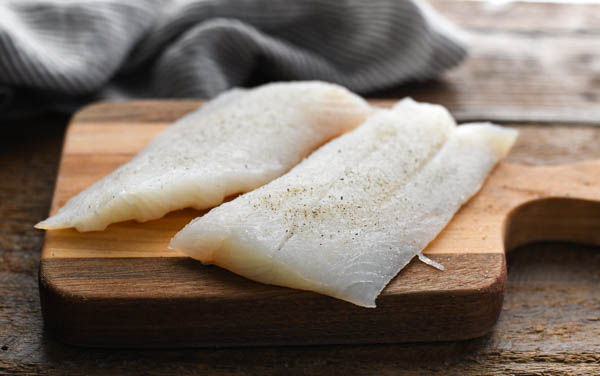 Two haddock fillets on a wooden cutting board