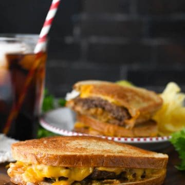 Patty melt sandwich on a cutting board with soda in the background
