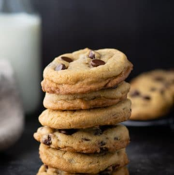 Stack of soft and chewy chocolate chip cookies on a dark surface