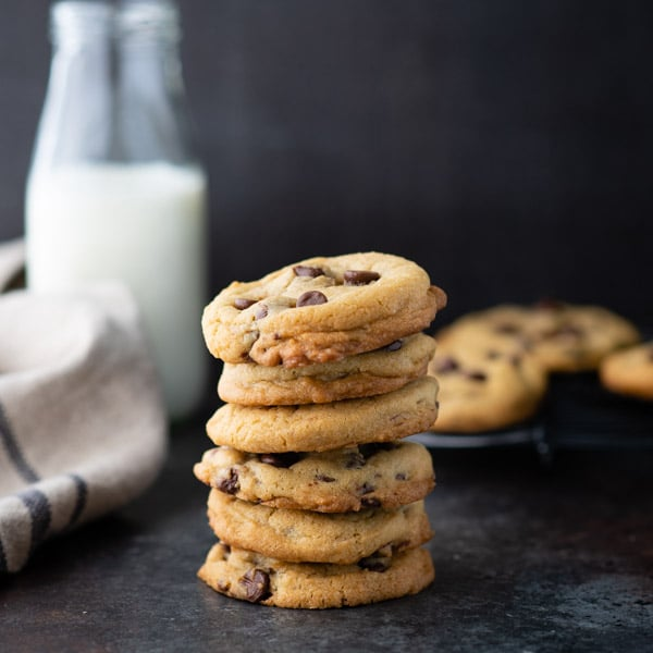Square image of a stack of soft and chewy chocolate chip cookies in front of a dark background