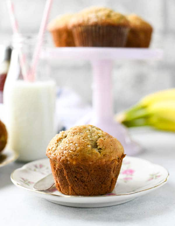 Side shot of easy banana muffins on a plate and cake stand.