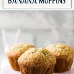 Moist banana muffins on a pink tray with text title box at top