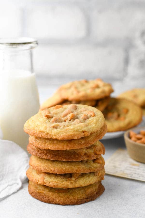 Stack of butterscotch cookies in front of a glass of milk