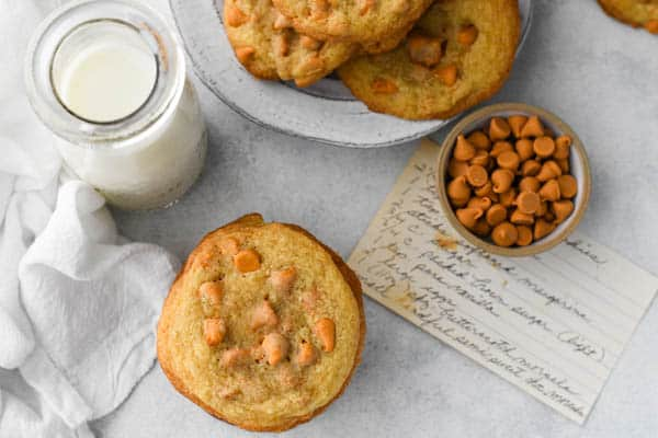 Overhead shot of cookies with butterscotch chips on a white table