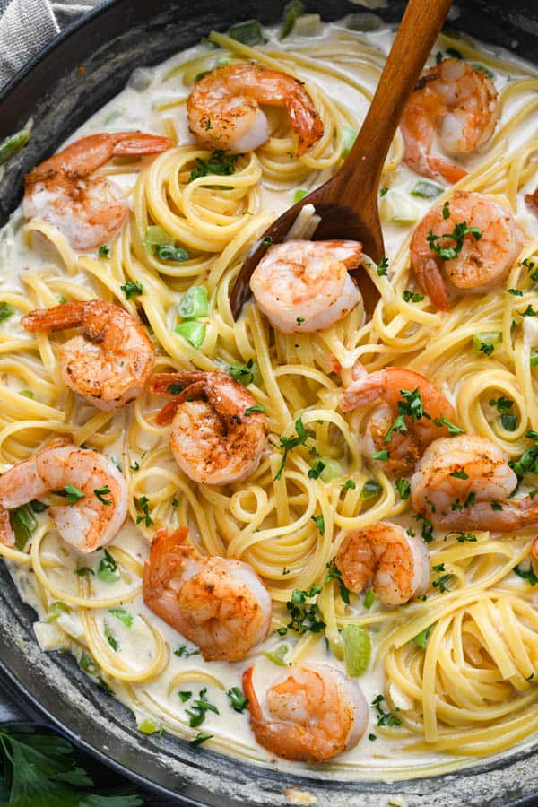 Close overhead shot of creamy Cajun shrimp pasta in a cast iron skillet.