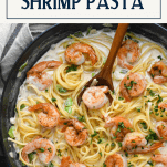 Creamy cajun shrimp pasta alfredo in a skillet with text title box at top
