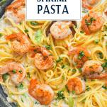 Creamy cajun shrimp pasta alfredo in a pan with text title overlay