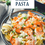 Side shot of a bowl of shrimp pasta with text title overlay