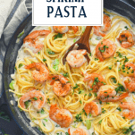 Overhead shot of a skillet full of cajun shrimp pasta with text title overlay