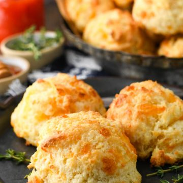 Close up side shot of fluffy cheese drop biscuits on a plate